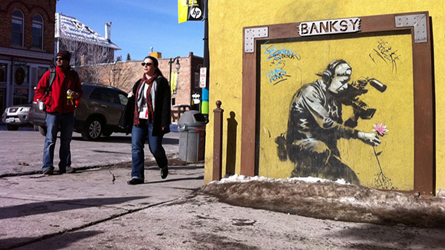 A man is being charged and fined for vandalising two Banksy pieces